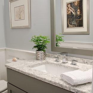 Idee per un piccolo bagno di servizio classico con ante con riquadro incassato, ante grigie, WC monopezzo, pareti blu, pavimento in pietra calcarea, lavabo sottopiano, top in quarzo composito e pavimento grigio