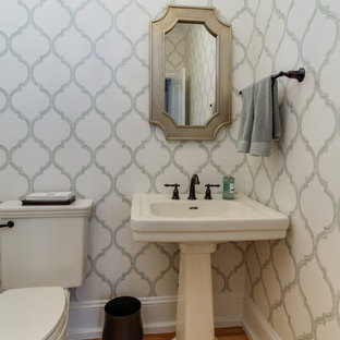 Photo of a medium sized country cloakroom in Raleigh with a two-piece toilet, multi-coloured tiles, white walls, light hardwood flooring, a pedestal sink and multi-coloured floors.