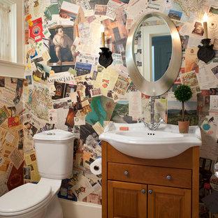 Klassische Gästetoilette mit integriertem Waschbecken, profilierten Schrankfronten, hellbraunen Holzschränken, Terrakottaboden, Wandtoilette mit Spülkasten, orangefarbenen Fliesen und bunten Wänden in Sonstige