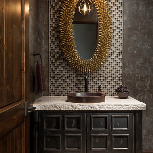 Photo of a large cloakroom in Phoenix with freestanding cabinets, dark wood cabinets, multi-coloured tiles, mosaic tiles, a vessel sink, black walls, travertine flooring, concrete worktops, white floors and grey worktops.