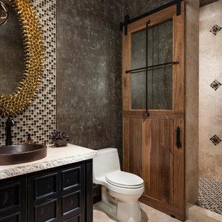 Ejemplo de aseo de estilo americano, grande, con armarios tipo mueble, sanitario de una pieza, baldosas y/o azulejos multicolor, paredes negras, suelo de travertino, lavabo sobreencimera, puertas de armario con efecto envejecido y baldosas y/o azulejos en mosaico