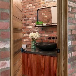 タンパのコンテンポラリースタイルのおしゃれなトイレ・洗面所 (フラットパネル扉のキャビネット、中間色木目調キャビネット、赤い壁、濃色無垢フローリング、ベッセル式洗面器、茶色い床、黒い洗面カウンター、フローティング洗面台、レンガ壁) の写真