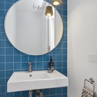 Cette image montre un petit WC et toilettes design avec un WC à poser, un carrelage bleu, des carreaux de porcelaine, un mur bleu et un lavabo suspendu.