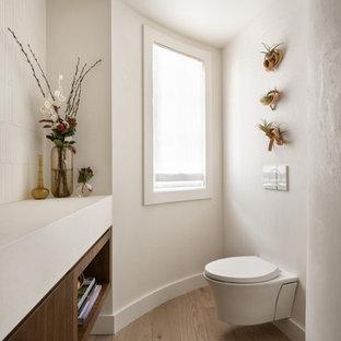 Стильный дизайн: туалет среднего размера в стиле модернизм с плоскими фасадами, фасадами цвета дерева среднего тона, инсталляцией, белой плиткой, плиткой из известняка, белыми стенами, светлым паркетным полом, врезной раковиной, столешницей из известняка, бежевым полом, белой столешницей и подвесной тумбой - последний тренд