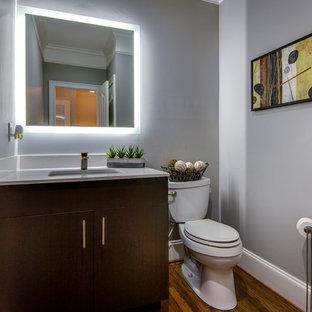 Immagine di un bagno di servizio minimal con ante lisce, ante in legno bruno, WC a due pezzi, pareti grigie, lavabo sottopiano, pavimento in legno massello medio e top bianco