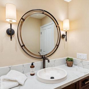 Cette image montre un grand WC et toilettes traditionnel avec un placard avec porte à panneau encastré, des portes de placard marrons, un WC suspendu, un mur beige, un sol en travertin, une vasque, un plan de toilette en quartz modifié, un sol beige, un plan de toilette blanc et meuble-lavabo encastré.
