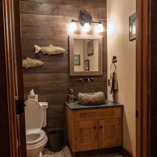 Idée de décoration pour un petit WC et toilettes chalet avec un placard à porte shaker, des portes de placard en bois brun, un WC séparé, un mur beige, un sol en carrelage de céramique, une vasque, un plan de toilette en stéatite et un sol beige.