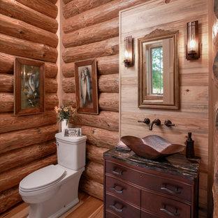 Cette image montre un WC et toilettes chalet en bois avec un placard en trompe-l'oeil, des portes de placard en bois sombre, un sol en bois brun, une vasque, un sol marron et un plan de toilette noir.