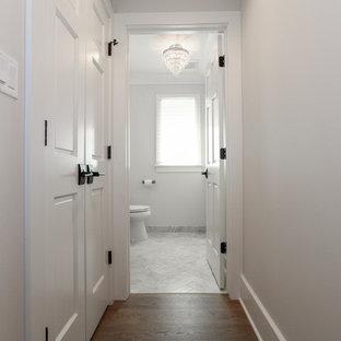 Ispirazione per un bagno di servizio country di medie dimensioni con consolle stile comò, ante nere, WC a due pezzi, pareti grigie, pavimento in marmo, lavabo sottopiano, top in cemento e pavimento grigio