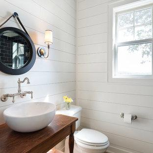 На фото: туалет среднего размера в морском стиле с раздельным унитазом, белыми стенами, настольной раковиной, столешницей из дерева, коричневым полом, фасадами островного типа, темными деревянными фасадами, темным паркетным полом и коричневой столешницей