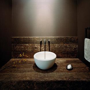 Diseño de aseo rural, pequeño, con paredes marrones, lavabo sobreencimera y encimera de madera