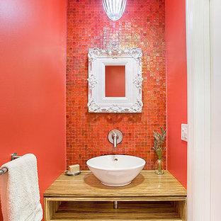 Ejemplo de aseo actual, pequeño, con armarios abiertos, puertas de armario de madera oscura, baldosas y/o azulejos rojos, baldosas y/o azulejos en mosaico, paredes rojas, suelo con mosaicos de baldosas, lavabo sobreencimera, encimera de madera, suelo rojo y encimeras marrones