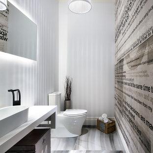 Diseño de aseo actual con lavabo sobreencimera, armarios tipo mueble, sanitario de dos piezas y paredes blancas