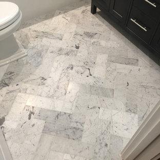Aménagement d'un petit WC et toilettes classique avec un placard à porte shaker, des portes de placard noires, un WC séparé, un carrelage gris, un mur blanc, un sol en marbre, un lavabo encastré, un plan de toilette en marbre et des carreaux en allumettes.