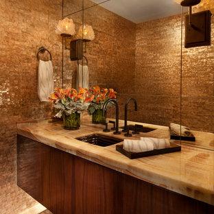Immagine di un bagno di servizio minimal con lavabo sottopiano, ante in legno scuro, top in onice, piastrelle beige, pareti beige e ante lisce