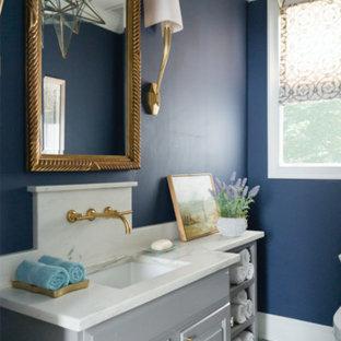 Idee per un piccolo bagno di servizio bohémian con consolle stile comò, ante grigie, WC monopezzo, pareti blu, pavimento in cementine, lavabo sottopiano, top in marmo, pavimento blu e top bianco