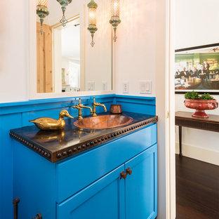Стильный дизайн: маленький туалет в средиземноморском стиле с синими фасадами, белыми стенами, темным паркетным полом, накладной раковиной, столешницей из меди, фасадами в стиле шейкер, унитазом-моноблоком, коричневым полом и фиолетовой столешницей - последний тренд