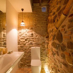 Esempio di un piccolo bagno di servizio stile rurale con WC a due pezzi, pareti beige, lavabo rettangolare e pavimento in mattoni