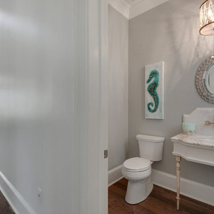 Design ideas for a small coastal cloakroom in Miami with a two-piece toilet, multi-coloured tiles, stone slabs, grey walls, medium hardwood flooring, marble worktops and a submerged sink.