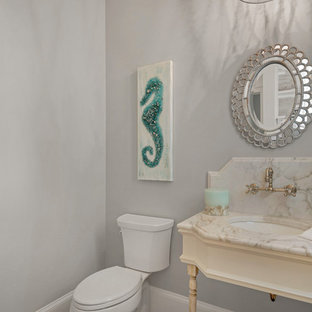 Inspiration for a small nautical cloakroom in Miami with a two-piece toilet, multi-coloured tiles, stone slabs, grey walls, medium hardwood flooring, marble worktops and a submerged sink.
