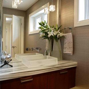 Cette image montre un WC et toilettes design de taille moyenne avec une vasque, un placard à porte plane, des portes de placard en bois sombre, un mur beige, un sol en bois brun, un plan de toilette en marbre et un plan de toilette multicolore.