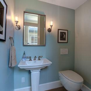 Ispirazione per un bagno di servizio chic di medie dimensioni con WC sospeso, pareti blu, pavimento in legno massello medio, lavabo a colonna e pavimento marrone