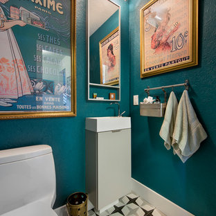 Example of a small eclectic porcelain floor and multicolored floor powder room design in Denver with a one-piece toilet, blue walls, flat-panel cabinets, gray cabinets and a console sink