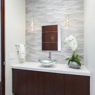 Пример оригинального дизайна: туалет среднего размера в стиле модернизм с плоскими фасадами, темными деревянными фасадами, серой плиткой, белыми стенами, настольной раковиной, столешницей из искусственного кварца и белой столешницей
