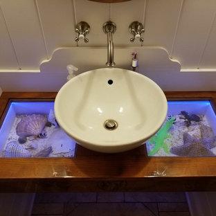 На фото: туалет среднего размера в морском стиле с белыми стенами, настольной раковиной и стеклянной столешницей