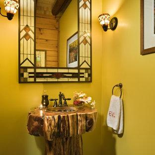 На фото: туалет в стиле рустика с раковиной с пьедесталом, желтыми стенами и полом из галечной плитки с