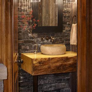 Пример оригинального дизайна интерьера: туалет в стиле рустика с настольной раковиной, столешницей из дерева, серой плиткой и каменной плиткой
