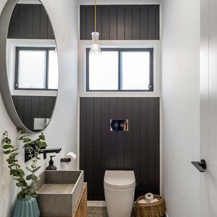 Aménagement d'un WC et toilettes bord de mer avec un placard à porte plane, des portes de placard en bois brun, un WC à poser, un mur blanc, béton au sol, une vasque, un plan de toilette en bois et un plan de toilette marron.