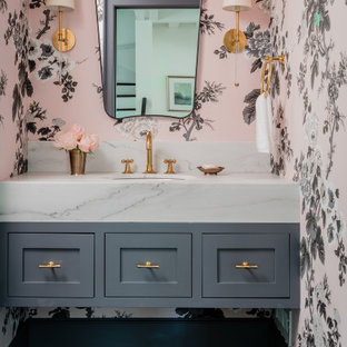 Cette image montre un WC et toilettes traditionnel de taille moyenne avec un sol en carrelage de céramique, un lavabo encastré, un plan de toilette en marbre, un plan de toilette blanc, un placard à porte shaker, des portes de placard grises, un mur rose, un sol noir, meuble-lavabo suspendu et du papier peint.
