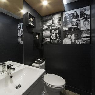 На фото: маленькие туалеты в современном стиле с фасадами островного типа, белыми фасадами, унитазом-моноблоком, белой плиткой, керамической плиткой, черными стенами, полом из керамической плитки, раковиной с несколькими смесителями и коричневым полом