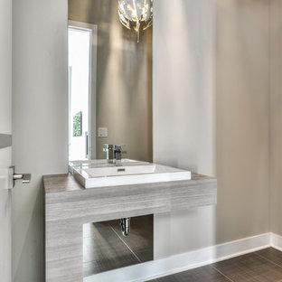 Создайте стильный интерьер: туалет среднего размера в стиле модернизм с светлыми деревянными фасадами, коричневой плиткой, серой плиткой, керамической плиткой, серыми стенами, полом из керамической плитки и столешницей из ламината - последний тренд