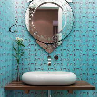Идея дизайна: туалет в стиле современная классика с настольной раковиной, столешницей из дерева, синими стенами и коричневой столешницей