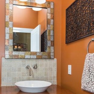 Réalisation d'un petit WC et toilettes tradition avec un placard en trompe-l'oeil, des portes de placard en bois brun, un WC séparé, un carrelage blanc, un carrelage de pierre, un mur orange, un plan de toilette en bois, une vasque et un plan de toilette marron.