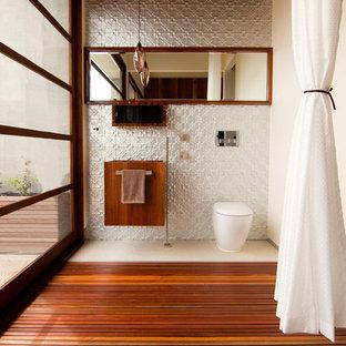 Idéer för att renovera ett funkis toalett, med grå kakel, vita väggar och mellanmörkt trägolv