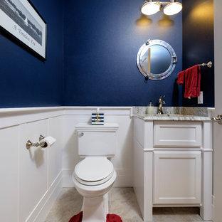 他の地域の小さいトランジショナルスタイルのおしゃれなトイレ・洗面所 (落し込みパネル扉のキャビネット、白いキャビネット、分離型トイレ、白いタイル、石タイル、青い壁、トラバーチンの床、アンダーカウンター洗面器、御影石の洗面台) の写真