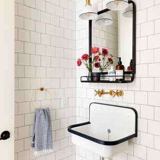 Inspiration for a country white tile powder room remodel in Minneapolis with white walls and a wall-mount sink