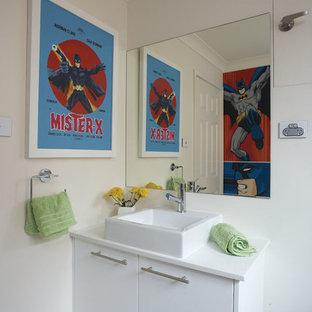 Свежая идея для дизайна: маленький туалет в стиле ретро с настольной раковиной, плоскими фасадами, белыми фасадами, столешницей из искусственного кварца, унитазом-моноблоком, белой плиткой, белыми стенами и полом из керамогранита - отличное фото интерьера