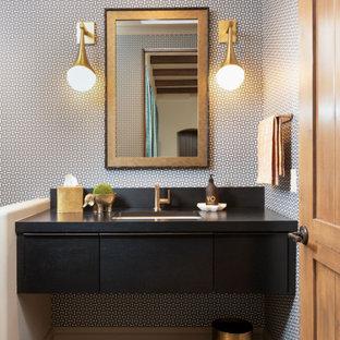 На фото: туалет среднего размера в стиле ретро с плоскими фасадами, черными фасадами, серыми стенами, полом из керамической плитки, врезной раковиной, столешницей из дерева, черным полом, черной столешницей, подвесной тумбой и обоями на стенах с