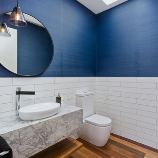 Inspiration for a mid-sized contemporary powder room in Melbourne with open cabinets, medium wood cabinets, a two-piece toilet, white tile, blue walls, medium hardwood floors, a vessel sink, brown floor, white benchtops and marble benchtops.