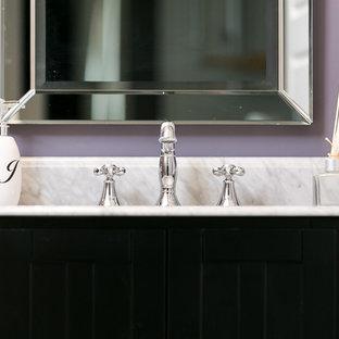 Diseño de aseo de estilo americano con armarios con puertas mallorquinas, puertas de armario negras, paredes púrpuras, lavabo bajoencimera y encimera de mármol