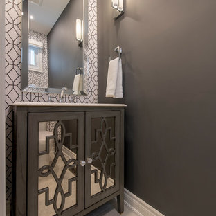 This is an example of a small contemporary cloakroom in Toronto with glass-front cabinets, grey cabinets, a one-piece toilet, grey walls, ceramic flooring, a submerged sink, solid surface worktops and beige floors.