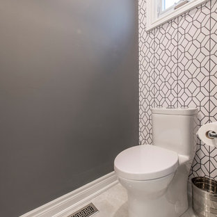Photo of a small contemporary cloakroom in Toronto with glass-front cabinets, grey cabinets, a one-piece toilet, grey walls, ceramic flooring, a submerged sink, solid surface worktops and beige floors.