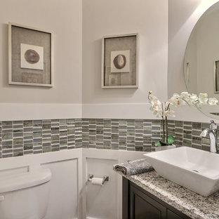 Cette image montre un WC et toilettes traditionnel de taille moyenne avec un placard avec porte à panneau encastré, des portes de placard en bois sombre, un carrelage multicolore, un carrelage en pâte de verre, un mur beige, une vasque et un plan de toilette en granite.