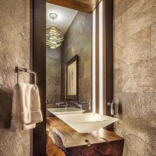 Kleine Urige Gästetoilette mit verzierten Schränken, dunklen Holzschränken, grauen Fliesen, grauer Wandfarbe, braunem Holzboden, Aufsatzwaschbecken, Waschtisch aus Holz, Zementfliesen, braunem Boden und brauner Waschtischplatte in Sonstige