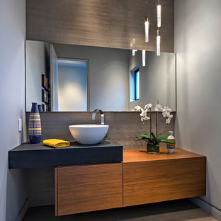 Aménagement d'un grand WC et toilettes moderne avec un placard à porte plane, des portes de placard en bois brun, un carrelage gris, des carreaux de porcelaine, un mur gris, un sol en carrelage de porcelaine, une vasque, un plan de toilette en béton, un sol gris et un plan de toilette noir.