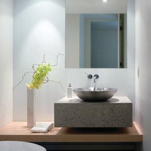 Неиссякаемый источник вдохновения для домашнего уюта: большой туалет в современном стиле с настольной раковиной, серой плиткой, унитазом-моноблоком, белыми стенами, полом из известняка и столешницей из известняка